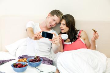 Paar mit Smartphone beim frühstücken im Bett
