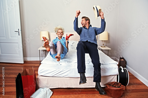 Leinwanddruck Bild couple in a hotel room with new red shoes