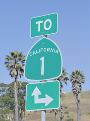 Roadsign on highway one in California, USA with palm trees