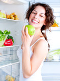Fototapety Beautiful Young Woman near the Refrigerator with healthy food