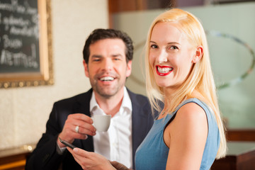Arbeitskollegen - Mann und Frau - in Cafe mit Tablet Computer