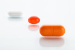 Three various pills: white, orange and red