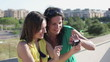 Two female friends taking photo with cellphone on terrace