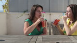Female friends drinking cocktails outdoors, tracking