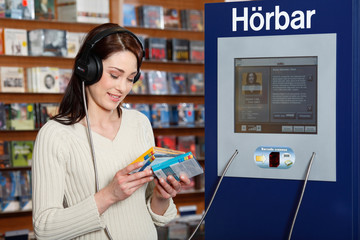 Frau in Buchhandlung hoert Hörbuch