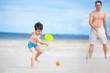 Father and son playing tennis on the beach