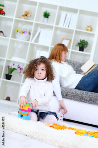 Child playing with  cubes at home with mother on sofa