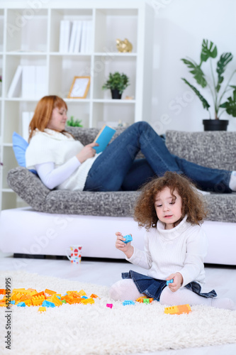 Cute girl playing while her mom is in the background