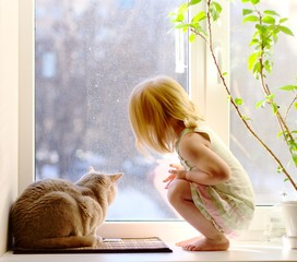 Cat and girl looking out of the window
