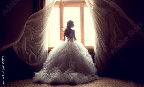 Leinwanddruck Bild The beautiful bride against a window indoors