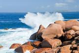 sea wave breaks against the pink granite rocks