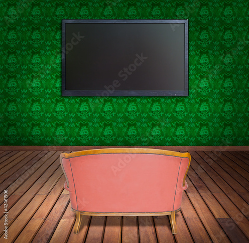 television and sofa in green wallpaper room