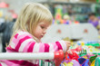 Adorable girl look to toys sit in shopping cart in supermarket