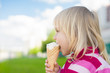 Adorable girl eat ice cream on green grass