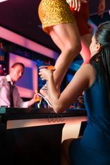 Frauen in einem Club oder Bar tanzen auf dem Tisch