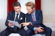 Zwei Geschäftsmänner schauen zusammen auf Tablet Computer