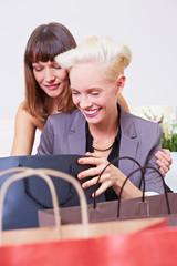 Glückliche Frauen betrachten Einkäufe