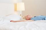 Fototapety Lachende Frau streckt sicht auf Bett aus