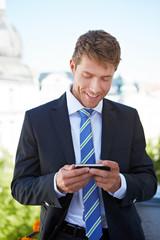 Mann schaut auf Display von Smartphone