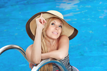 beautiful girl in the hat in the pool