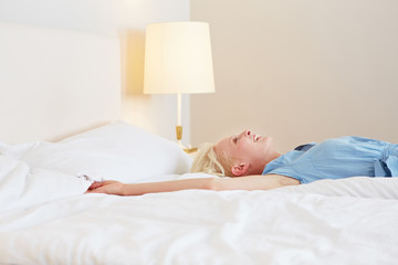 Lachende Frau streckt sicht auf Bett aus