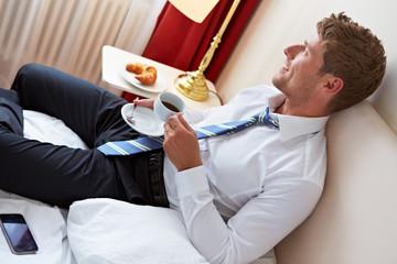 Geschäftsmann frühstückt im Bett