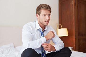 Geschäftsmann knöpft Hemd zu