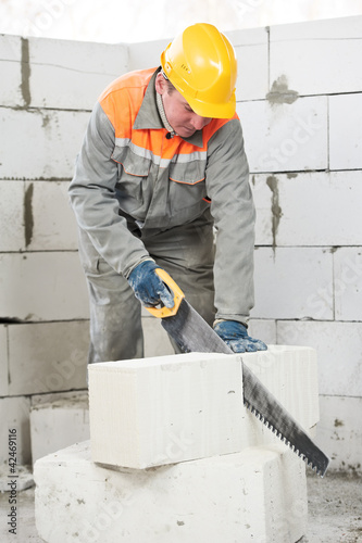 mason worker bricklayer with hand saw