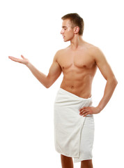 A nude young man covering himself with a towel,