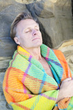 man sleeping wrapped in blanket
