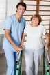 Therapist Assisting Senior Woman To Walk With The Support Of Bar
