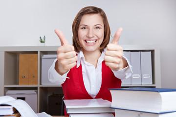 Frau beim Lernen hält beide Daumen hoch
