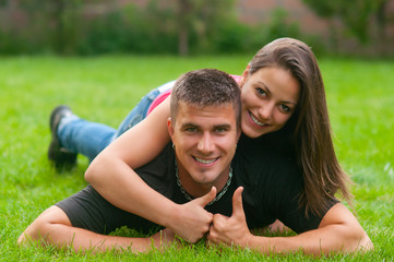 Young couple in love lying on the grass with thumbs up