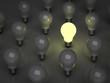 One glowing light bulb amongs unlit bulbs