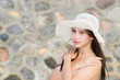 Beautiful woman with hat smiling on a blur wall background