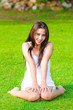 Beautiful healthy Young Woman sitting on the green grass