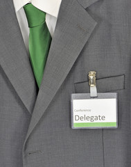 Male gray business suit, green tie and conference badge
