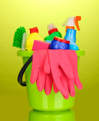 Bucket with cleaning items on green background