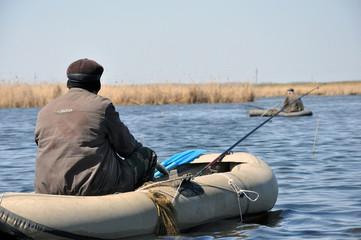 Рыбаки на резиновых лодках с удочками в ожидании поклевки