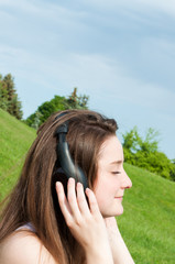 Young girl listens to music with headphones close up.