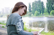 Girl sitting outdoors using a touchscreen tablet along a riverba