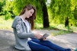 Girl sitting outdoors using a touchscreen tablet