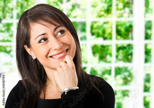 Smiling businesswoman thinking at something