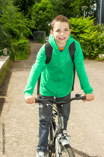 Young school boy with backpack on a bicycle