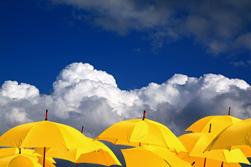 yellow umbrellas on cloudy background