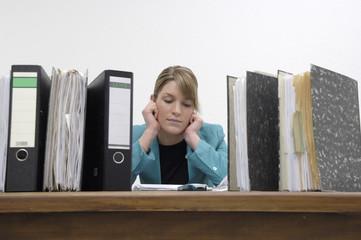 Sekretärin sitzt nachdenklich über ihre Akten