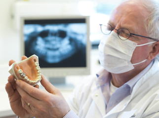 adult dentist looking at dentures