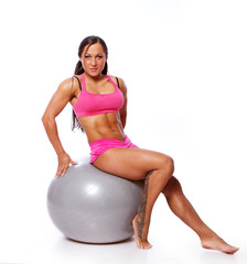 Portrait of joga trainer posing in studio with fitball
