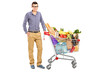 A young male posing next to a shopping cart full with groceries