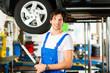 Mechaniker in Werkstatt arbeitet an Auto